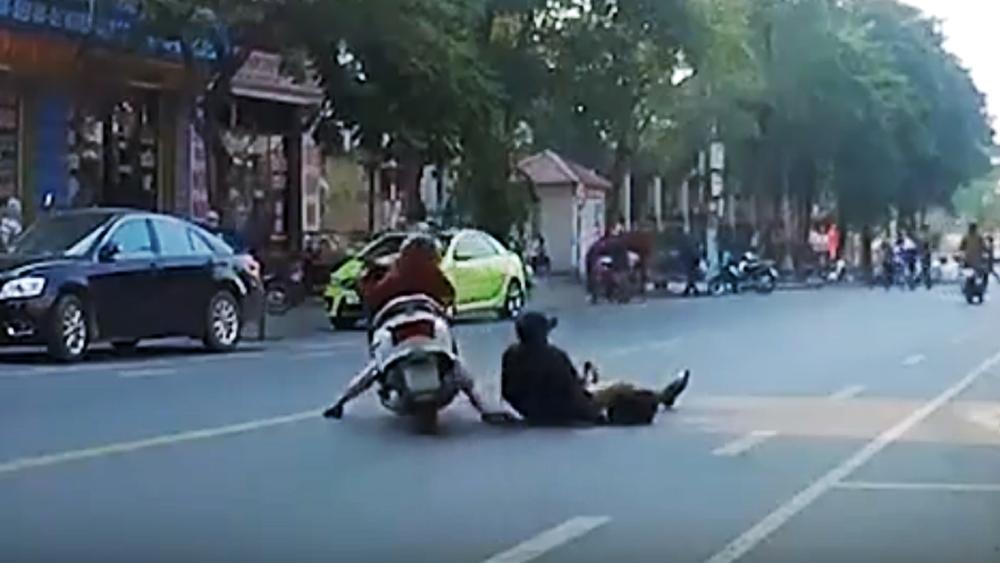 Người đàn ông thong thả đi bộ giữa đường bị xe máy tông từ phía sau